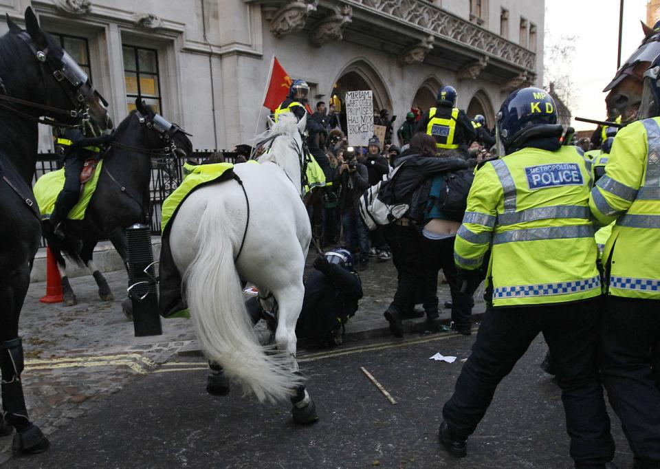 A police rider on the floor after he was pulled off his horse by protestors in London, Thursday, Dec. 9, 2010. Police clashed with protesters marching to London's Parliament Square as lawmakers debated a controversial plan to triple university tuition fees in England. (AP Photo/Alastair Grant)