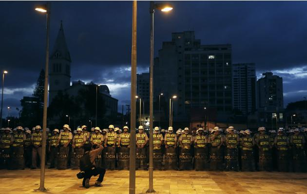 A photographer takes pictures of military policemen before a protest against the 2014 World Cup, in Sao Paulo