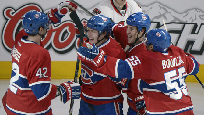 Montreal Canadiens' Brendan Gallagher (11) celebrates with teammates Jarred Tinordi (42), Brandon Prust (8) and Francis Bouillon (55) after scoring against the Ottawa Senators during second-period NHL hockey Game 2 first-round playoff action in Montreal, Friday, May 3, 2013. (AP Photo/The Canadian Press, Graham Hughes)