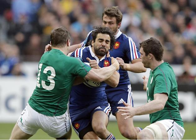 France's Yoann Huget, center, is grabbed by Ireland's Brian O'Driscoll, left, and Ireland's Peter O'Mahony during the Six Nations Rugby Union match between France and Ireland at th