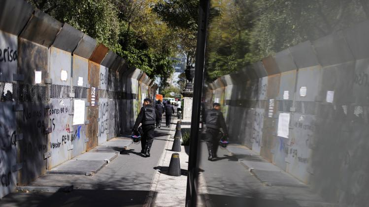 Riot policemen walk along a fence surrounding the perimeter of the Senate building in Mexico City