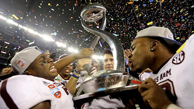 Texas A&M defensive backs Tramain Jacobs, left, and Steven Terrell celebrate with the trophy after the Cotton Bowl NCAA college football game against Oklahoma Friday, Jan. 4, 2013, in Irving, Texas. Texas A&M  won 41-13. (AP Photo/LM Otero)