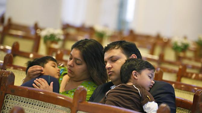 An Indian Christian family falls asleep while attending an early morning Easter Mass in Bangalore, India, Sunday, March 31, 2013.  (AP Photo/Aijaz Rahi)