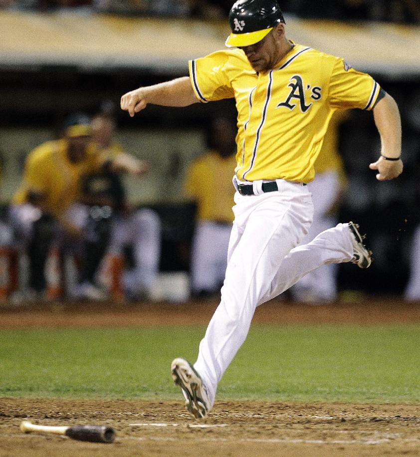 Oakland Athletics' Brandon Moss scores against the Texas Rangers in the fifth inning of a baseball game, Tuesday, Oct. 2, 2012, in Oakland, Calif. Moss scored on a single by Derek Norris. (AP Photo/Ben Margot)