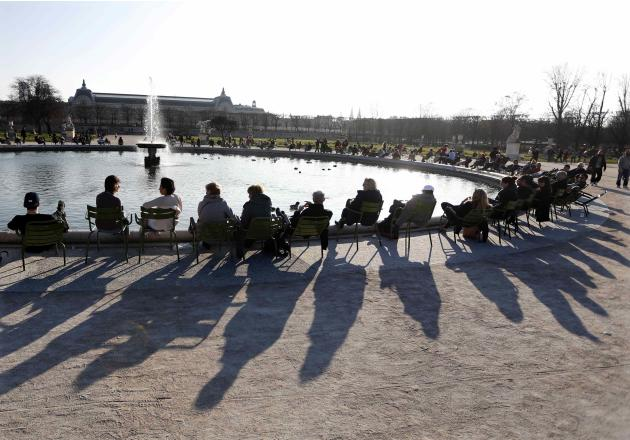 Shadows are cast as people relax in chairs around a fountain in the Tuileries Garden in central Paris during a warm and sunny winter day