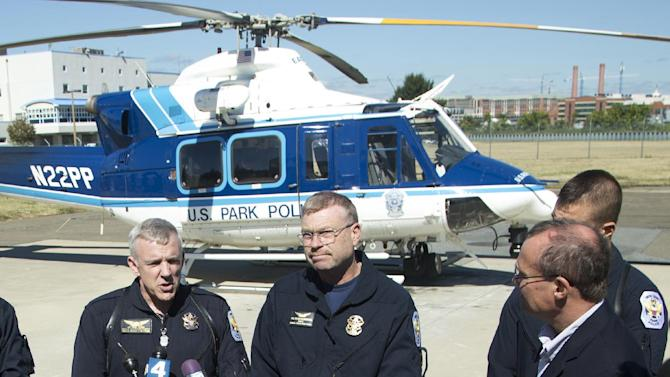 U.S. Park Police Aviation Division Rescue Technician Sgt. Dave Tolson, left, helicopter pilot Sgt. Kenneth Burchell, center, and Officer Michael Abate, obscured, talk to reporters about their operation flying over the Navy Yard, during a news conference at the U. S. Park Police Anacostia Station in Washington, Tuesday, Sept. 17, 2013. A dozen people died in a shooting rampage Monday at the Washington Navy Yard. (AP Photo/Manuel Balce Ceneta)