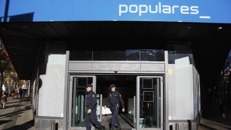 Police officers leave ruling People's Party headquarters in Madrid