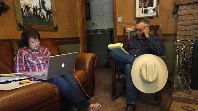 """Cliven Bundy, right, and his wife Carol Bundy make calls and look online at their ranch near Bunkerville Nev. Saturday, April 5, 2014. The Bureau of Land Management has begun to round up what they call """"trespass cattle"""" that rancher Cliven Bundy has been grazing in the Gold Butte area 80 miles northeast of Las Vegas. (AP Photo/Las Vegas Review-Journal, John Locher)"""