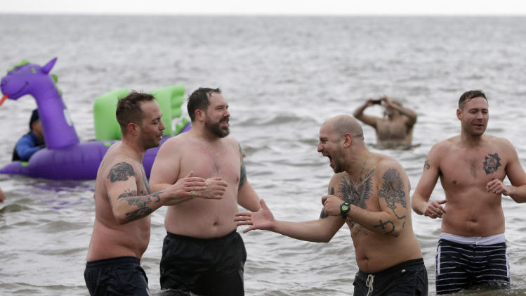 Tattooed men congratulate each other on taking the plunge during the 110th annual Coney Island Polar Bear Club ocean swim at Coney Island in New York, Tuesday, Jan. 1, 2013.  (AP Photo/Kathy Willens)