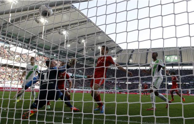 Bayern's Thomas Mueller scores a goal against Wolfsburg goalkeeper Diego Benaglio during their German first division Bundesliga soccer match in Wolfsburg