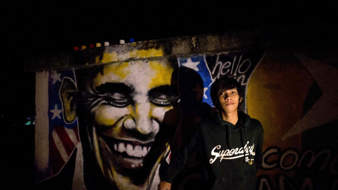 Artist Arker Kyaw poses with the graffiti welcoming U.S. President Barack Obama in Yangon, Myanmar, at dawn on Saturday, Nov. 17, When Arker Kyaw heard Obama was coming to Myanmar, he gathered 15 cans of spray paint and headed for a blank brick wall under cover of darkness. Kyaw, whose passion is graffiti, labored from 3 am until the sun came up. (AP Photo/Gemunu Amarasinghe)