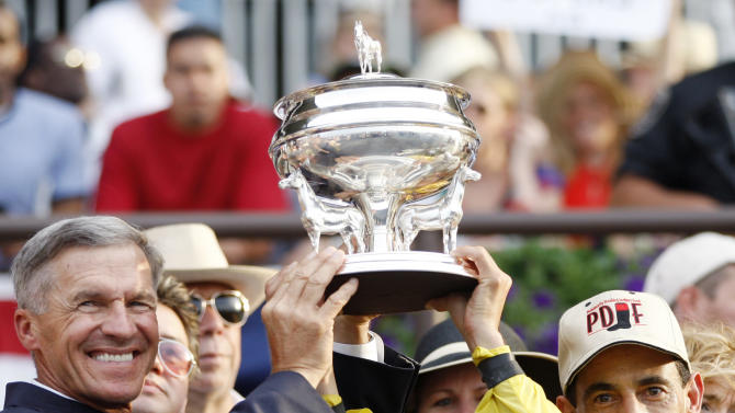 Trainer Michael Matz, left, and jockey John Velazquez hoist the trophy after Velazquez rode Union Rags to the win in the Belmont Stakes horse race at Belmont Park in Elmont, N.Y., on Saturday, June 9, 2012. (AP Photo/Mike Groll)