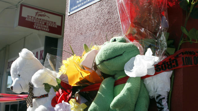 Flowers and stuffed animals are left at a memorial at Fero's Bar and Grill in Denver on Thursday, Oct. 18, 2012. The bodies of a man and four woman were discovered after firefighters extinguished a fire at the bar early Wednesday morning. Police have arrested three suspects in the case.(AP Photo/Ed Andrieski)