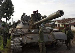 Congolese soldiers arrive atop a tank in Bunagana