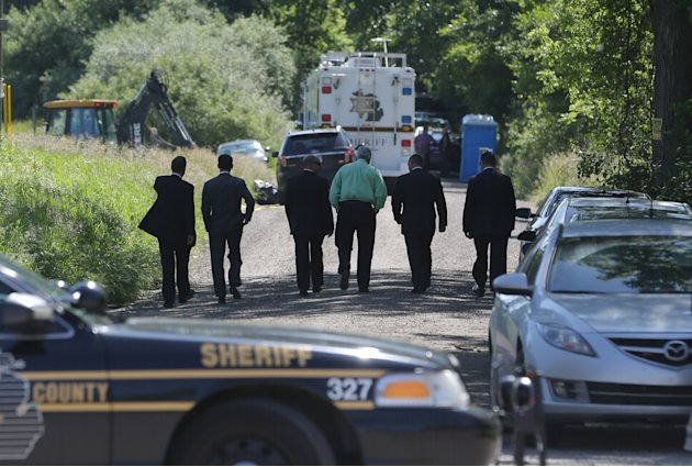 Law enforcement officials walk back to the search area after Robert Foley, special agent in charge of the FBI's Detroit division, addressed the media in Oakland Township, Mich., Wednesday, June 19, 20