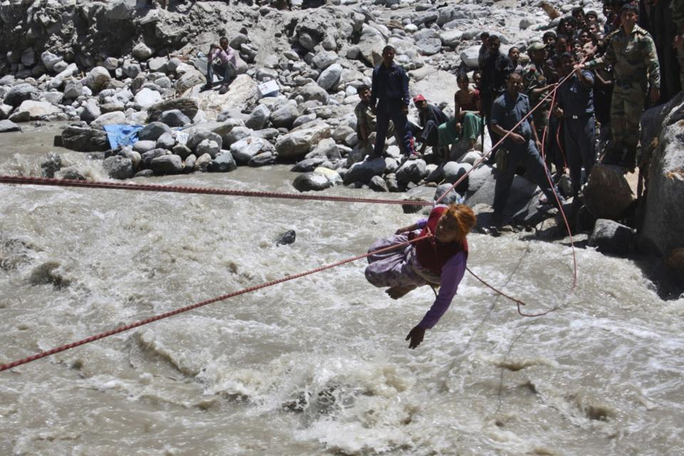 Indian army soldiers make a stranded pilgrim to cross over a river with the help of a rope near Hemkunsaheb, India, Saturday, June 22, 2013. Soldiers were working to evacuate tens of thousands of people still stranded Saturday in northern India where nearly 600 people have been killed in monsoon flooding and landslides. (AP Photo)