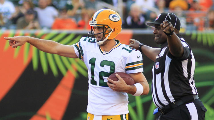 Green Bay Packers quarterback Aaron Rodgers (12) points out something to official Lemuel Hawkins in the first half of an NFLpreseason football game against the Cincinnati Bengals, Thursday, Aug. 23, 2012, in Cincinnati. (AP Photo/Al Behrman)
