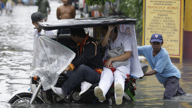 CORRECTS THE NAME OF TYPHOON IN SECOND SENTENCE - A Filipino man pushes a tricycle as passengers try to avoid floodwaters in Manila, Philippines on Tuesday Aug. 2, 2011. Typhoon Muifa continues to blow away from the northern Philippines after killing at least 4 people even though it did not make landfall. Classes were suspended on Tuesday in most parts of the metro due to floods. (AP Photo/Aaron Favila)