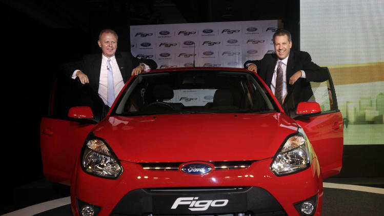 FILE - In this Tuesday, March 9, 2010 file photo, Ford Vice President and President Asia pacific and Africa Joe Hinrichs, right, and President and Managing Director Ford India Michael Boneham, left, pose with the newly launched Figo car in New Delhi, India. Ford Motor Co.'s Indian subsidiary is recalling nearly 130,000 of its most popular cars. The manufacturing defects date back as far as 2008 and can cause fire and other problems, the company said late Monday, Aug. 13, 2012. (AP Photo/Manish Swarup, File)