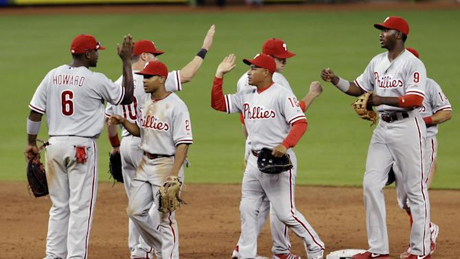 Philadelphia Phillies players celebrate their 2-1 win against the Miami Marlins after a baseball game in Miami, Sunday, April 14, 2013. (AP Photo/Alan Diaz)
