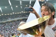 Juventus goalkeeper Gianluigi Buffon kisses the Serie A trophy, the Scudetto, during the post-match ceremony on May 13. The victory meant Juve took their unbeaten run in all competitions to 43 games, including the final match of last season, a record for an Italian team