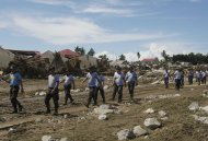 Philippine police prepare to search for victims during retrieval operation Sunday, Dec. 18, 2011 in Iligan city in southern Philippines. Tropical storm Washi blew away Sunday after devastating the southern Philippines with flash floods that killed hundreds of people as they slept and turned two coastal cities into a muddy wasteland filled with overturned cars and uprooted trees. (AP Photo/Bullit Marquez)