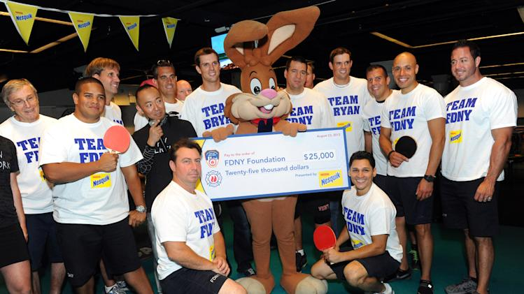 COMMERCIAL IMAGE - Gold medalists and champion tennis players Bob, second right of bunny, and Mike Bryan, left of bunny, present members of the FDNY with a check for $25,000 to the FDNY Foundation after the Nesquik FDNY Foundation Charity Ping Pong tournament at SPiN Galactic in New York, Thursday, Aug. 23, 2012.  The Bryan Brothers took on FDNY's ace ping pong players to pay tribute to and support the FDNY.  (Diane Bondareff/Invision for Nesquik/AP Images)