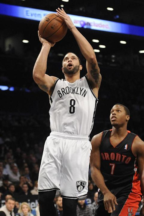 Brooklyn Nets' Deron Williams (8) goes to the basket in front of Toronto Raptors' Kyle Lowry (7) in the first half of an NBA basketball game on Monday, March 10, 2014 at Barclays Center in New