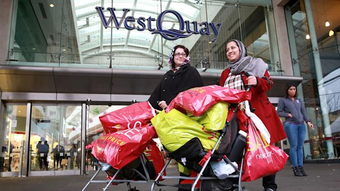 Khadija Iqbal, left and Marzia Rahimi walk with baby strollers full of shopping bags, during the Boxing Day sales, at a shopping centre in Southampton,  England, Friday Dec. 26, 2014. (AP Photo/PA, Matt Alexander) UNITED KINGDOM OUT