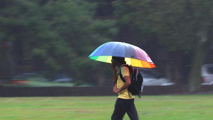 A man use an umbrella to fend off the rain as he walks through a park in Sydney, Australia, Monday, Jan. 28, 2013. Torrential rain over the weekend flooded several towns in eastern Australia, and three deaths were reported. (AP Photo/Rick Rycroft)
