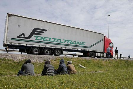Migrants gather near a truck on the road that leads to the Channel tunnel in the hopes of boarding to make a clandestine crossing, in Calais