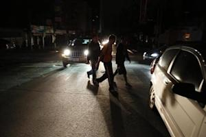 People walk on a street during a blackout in Caracas
