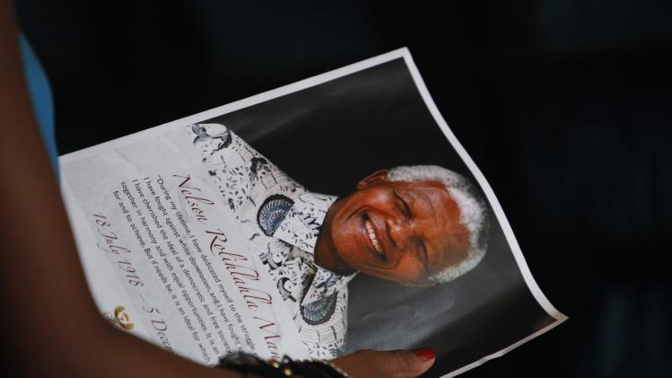 A choir girl holds a portrait of former South African President Mandela as they sing during a memorial service for him in Singapore
