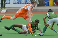 Seve van Ass of The Netherlands (L) leaps through defenders Ahmed Waseem (R) and Muhammad Ateeq of Pakistan (C) during their semi-final at the Champions Trophy in Melbourne. The Netherlands are in line to win their first Champions Trophy title for six years after outclassing Pakistan 5-2