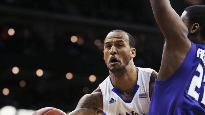 Kansas guard Travis Releford (24) passes around Kansas State forward Jordan Henriquez during the first half of an NCAA college basketball game for the Big 12 men's tournament title, Saturday, March 16, 2013, in Kansas City, Mo. (AP Photo/Orlin Wagner)