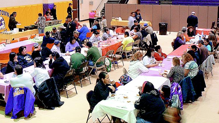 In this Nov. 19, 2012 photo community members eat and listen to speakers at a prayer service in New Town, N.D., where a woman and three of her grandchildren were shot and killed on Sunday.  New Town is on an American Indian reservation called Fort Berthold.  (AP Photo/Minot Daily News, Flint McColgan)