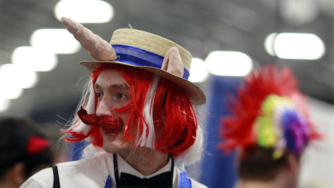 """Josiah Tyrrell, of Syracuse, N.Y., is dressed as the character Flam from the My Little Pony cartoons as he stands with others at """"BronyCon"""" Saturday, June, 30, 2012, in Secaucus, N.J. Scores of men in brightly colored costumes were among the 4,000 My Little Pony fans at this weekend's """"BronyCon"""" gathering in New Jersey for fans of a My Little Pony cartoon.  (AP Photo/Mel Evans)"""