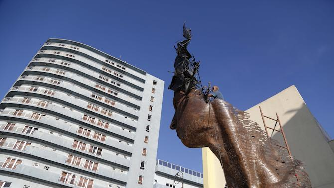 A worker gives the final touches to¨Primavera,¨ a creation dedicated to Cuban women, by Cuban artist Rafael San Juan in Havana, Cuba, Saturday, May 23, 2015. The sculpture is part of the month long Havana Biennial Art Fair. The event opened Friday with works by artists from 40 countries at museums, galleries and outdoor spaces around Cuba's capital. (AP Photo/Desmond Boylan)