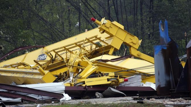 Heavy cranes are covered by debris from Contract Fabricators Inc. after a tornado ripped through the area Thursday, April 11, 2013. A man who was working at the site was killed and another was injured. A strong spring storm that socked the Midwest with ice and heavy, wet snow made its way east, raking the South with tornadoes Thursday, with three deaths blamed on the rough weather and thousands of people without power. (AP Photo/Rogelio V. Solis)