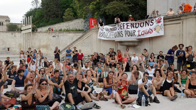 """Part-time and temporary arts workers, striking artists and theater personnel, known as 'intermittents', applaud, during a general assembly, in Avignon, France, Friday, July 4, 2014. Organizers of one of Europe's premier theater festivals are cancelling some shows amid a protest movement by cultural workers over changes to their off-season unemployment benefits. The director of the Festival d'Avignon, Olivier Py, told journalists in Avignon that two plays scheduled for Friday's opening night have been called off. The CGT union announced a strike, but it's unclear how many workers will take part. Banner reads :""""That we defend, we defend for all"""". (AP Photo/Claude Paris)"""