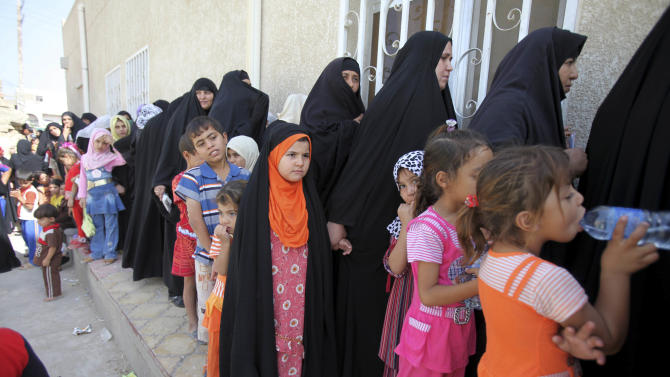 FILE - In this Wednesday, Sept. 9, 2009 Girls and women who are orphaned or widowed by violence line up for clothing in Baghdad, Iraq.  A study released Sunday Sept 18 2011 by a global humanitarian aid organization concluded that three out of every five widows in Iraq lost their husbands in the years of violence that followed the 2003 invasion. (AP Photo/Karim Kadim, File)