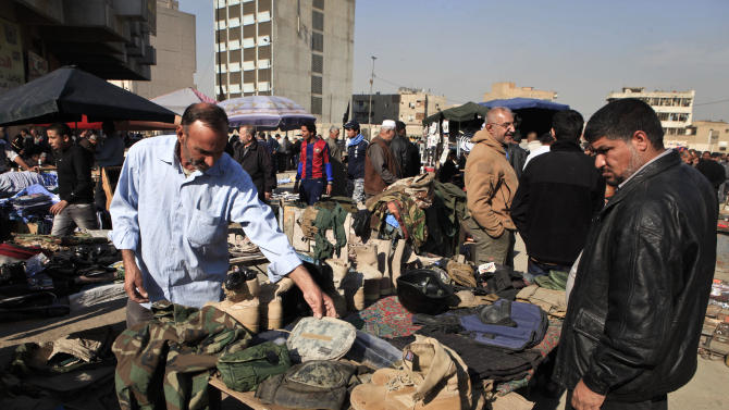 Street vendors sell used US army military gear in Baghdad, Iraq, Monday, Dec. 17, 2012. A year after the last American troops rumbled out of Iraq, the two countries are still trying to get comfortable with a looser, more nuanced relationship as the young democracy struggles to cope with ongoing political upheaval and the legacy of war. (AP Photo/ Karim Kadim)