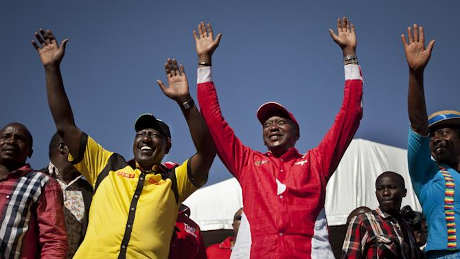 Kenyan Presidential candidate Uhuru Kenyatta, center right, and his running mate William Ruto, center left, greet the crowd as they arrive at the final election rally of Kenyatta's The National Alliance party at Uhuru Park in Nairobi, Kenya Saturday, March 2, 2013. Kenya's top two presidential candidates - Uhuru Kenyatta and Raila Odinga - held their final rallies Saturday before large and raucous crowds ahead of Monday's vote, which is the first nationwide election since Kenya's December 2007 vote descended into tribe-on-tribe violence that killed more than 1,000 people. (AP Photo/Ben Curtis)