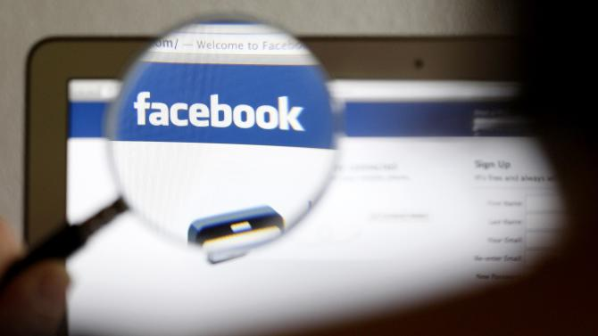 In this photo illustration, a Facebook logo on a computer screen is seen through a magnifying glass held by a woman in Bern