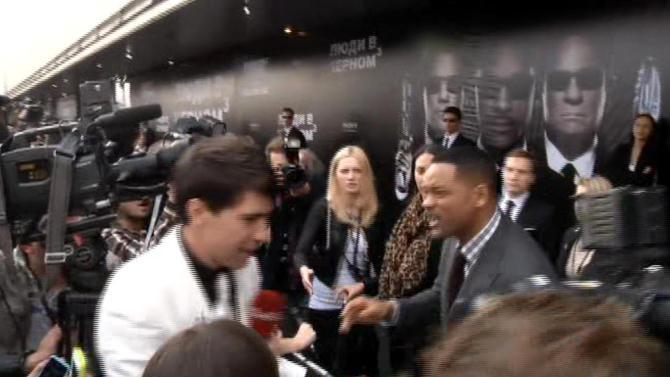"In this video image taken from AP video U.S. actor Will Smith, center right, reacts after he was embraced by reporter Vitalii Sediuk, white suit, from the Ukrainian television channel 1+1  on the red carpet before the premiere of ""Men in Black III"" Friday May 18, 2012 in Moscow. Hollywood star Will Smith has slapped a male television reporter who tried to kiss him before the Moscow premiere of ""Men in Black III."" Smith pushed him away and then slapped him lightly across the cheek with the back of his left hand.   (AP Photo via AP video)"