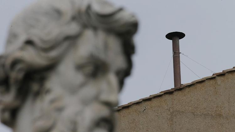 A statue dwarfs the chimney on the roof of the Sistine Chapel where cardinals will gather to elect the new pope during the conclave at the Vatican, Monday, March 11, 2013. (AP Photo/Dmitry Lovetsky)