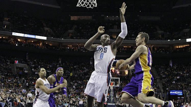 Los Angeles Lakers' Steve Nash, right, looks to pass around Charlotte Bobcats' Bismack Biyombo, second from right, as Charlotte Bobcats' Gerald Henderson, left, guards Los Angeles Lakers' Dwight Howard, second from left, during the first half of an NBA basketball game in Charlotte, N.C., Friday, Feb. 8, 2013. (AP Photo/Chuck Burton)