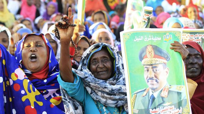 Woman holds a picture of Sudanese President Omar Hassan al-Bashir as Bashir attends a rally with Sufi supporters Hajj Yusuf at Khartoum district