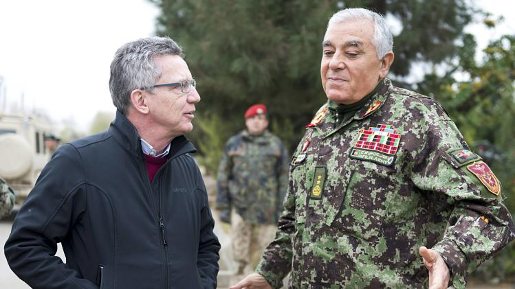 German Defence Minister de Maiziere speaks with the Afghan army commander, General Wesa, as they meet in Camp Shaheen outside Mazar-e-Sharif