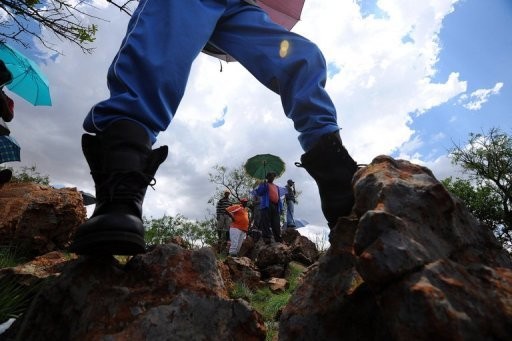 <p>Striking miners stage a protest on the hill at the AngloGold Ashanti mine in Carletonville, 84kms northwest of Johannesburg, on October 19. Thousands of gold miners returned to their shafts in South Africa on Friday after a pay deal to end the wave of strikes that had halted production of the precious metal, operators said.</p>